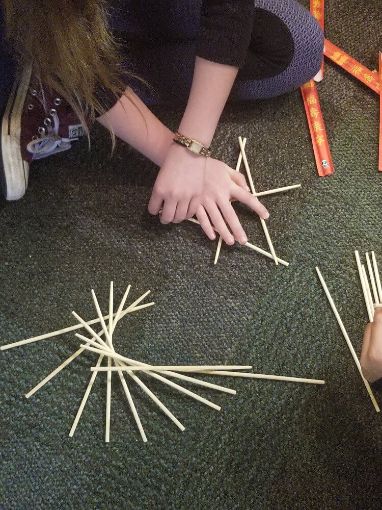 Students make a curve using straight lines (chopsticks) at an event organized by Fusion Academy of Westchester in White Plains