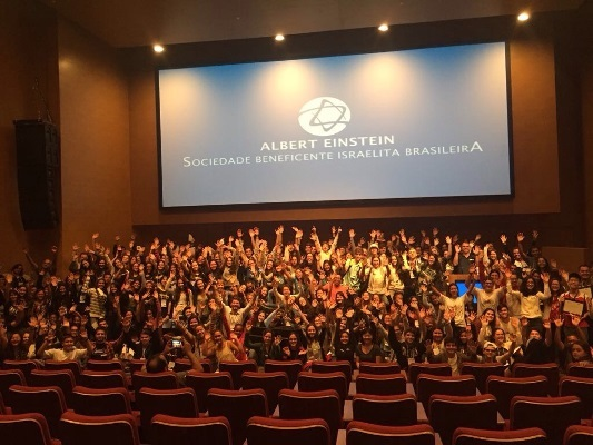 Brain Bee participants raise their hands at an event organized by Hospital Israelita Albert Einstein in Brazil