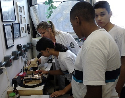 Students look into a microscope during an event organized by Núcleo de Extensão Museu 3D in Brazil