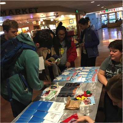 Children receive materials from an info table during an event organized by Pacific Lutheran University in Tacoma, Washington