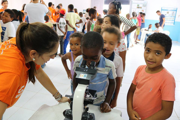 Children look through a microscope during an event organized by Santos Dumont Institute in Brazil