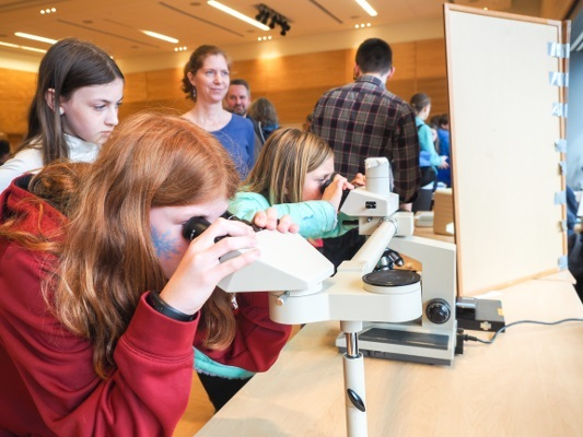 Children peer through microscopes at an activity station during an event organized by the University of Washington