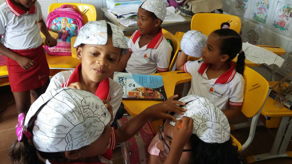 Students make paper brain hats during a classroom visit by Universidade Catolica do Salvador in Brazil